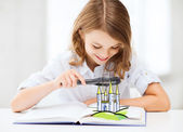 Girl with book looking to castle through magnifier — Stock fotografie