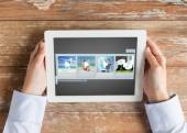 Close up of hands with video gallery on tablet pc — Stock Photo