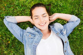 Smiling young girl with closed eyes lying on grass — Stock Photo