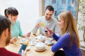 Group of friends with smartphones meeting at cafe — Stock Photo