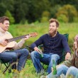 Group of tourists playing guitar in camping — Stock Photo #68597739