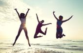 Happy female friends dancing and jumping on beach — Stock Photo