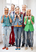 Happy friends covering faces with own photos — Stock Photo