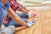 Close up of couple with ruler measuring flooring — Stock Photo