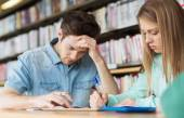 Students writing to notebooks in library — Stock Photo