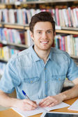 Happy student writing to notebook in library — Stock Photo