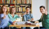 Students with books showing thumbs up in library — Stock Photo
