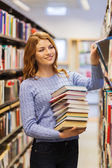 Happy student girl or woman with books in library — Stock Photo