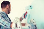 Close up van man in handschoenen houden schilderij roller — Stockfoto