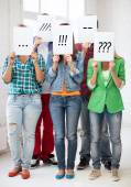 Friends or students covering faces with papers — Stock Photo