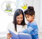 Happy mother and daughter reading fairytale book — Stock Photo