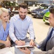 Happy couple with car dealer in auto show or salon — Stockfoto #68708875