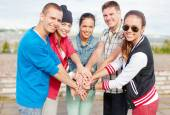 Teenagers hands on top of each other outdoors — Stock Photo
