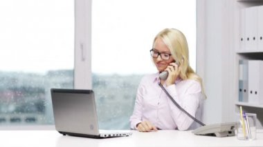 Smiling businesswoman with laptop calling on phone — Stock Video