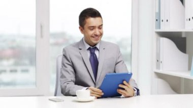 Smiling businessman with tablet pc drinking coffee — Stock Video