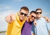 Smiling friends in sunglasses pointing at you — Stock Photo