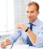 Uomo d'affari con gli occhiali, scrivendo nel notebook — Foto Stock