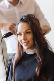 Happy woman with stylist making hairdo at salon — Stock Photo
