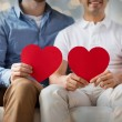 Close up of happy gay male couple with red hearts — Stock Photo #69307225