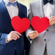 Close up of male gay couple holding red hearts — Stock Photo #69307315