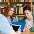 Happy students with tablet pc in library — Stock Photo #69307695