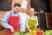 Happy couple and male chef cook cooking in kitchen — Stock Photo