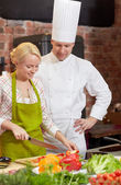Happy male chef cook with woman cooking in kitchen — Stock Photo