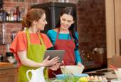 Happy women with tablet pc cooking in kitchen — Stock Photo