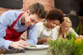 Happy friends cooking and decorating dishes — Stock Photo