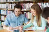 Ευτυχισμένος φοιτητές εγγράφως να σημειωματάρια στη βιβλιοθήκη — Φωτογραφία Αρχείου