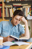 Male student reading book in library — Stock Photo
