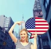 Smiling woman with text bubble of american flag — Stock Photo