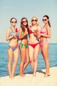 Group of smiling women eating ice cream on beach — Stock Photo