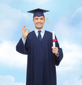 Smiling adult student in mortarboard with diploma — Stock Photo