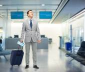 Happy businessman in suit with travel bag — Stock Photo