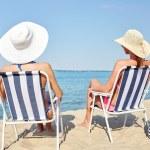 Happy women sunbathing in lounges on beach — Stock Photo #69827035