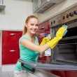 Happy woman cleaning cooker at home kitchen — Stock Photo #69828043