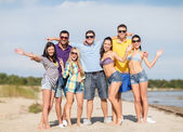 Group of happy friends waving hands on beach — Stock Photo