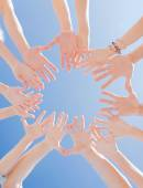 Many hands over blue sky background — Stock Photo