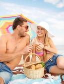 Chappy ouple having picnic and sunbathing on beach — Stock Photo