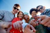 Happy teenage friends pointing fingers on street — Stock Photo
