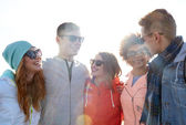 Happy teenage friends in shades talking on street — Stock Photo