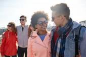 Happy teenage friends in shades talking on street — Stock Photo