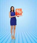 Happy young woman in dress with red sale sign — Stock Photo