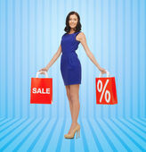 Happy young woman in dress with red shopping bags — Stock Photo