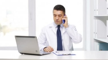 Doctor with laptop calling on smartphone — Wideo stockowe