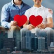 Close up of happy gay male couple with red hearts — Stock Photo #70200219