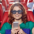 Happy woman with smartphone in 3d movie theater — Stock Photo #70200447