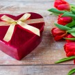 Close up of red tulips and chocolate box — Stock Photo #70200815