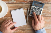 Close up of hands with calculator and notebook — Stock Photo